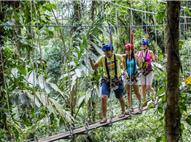 Three tourists walking on small bridge hanging with cables and wearing a harness and helmets