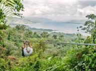 Man sliding on zip line in the forest with the Arenal Lake in the background