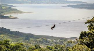 Man sliding on canopy zip line and panoramic view of forest and Arenal Lake