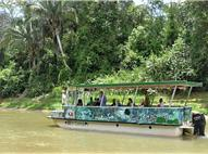 Roofed boat transporting tourists on the river and the forest beside