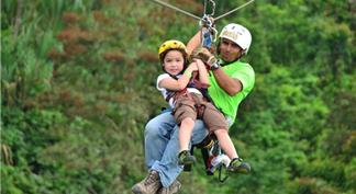 Child with guide sliding on zip line