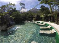 Swimming pool hot springs with benches and cascade and the Arenal Volcano in the background on a sunny day