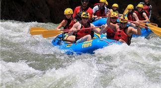 Tourists on two blue rafts going down a rapid