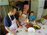 Mujer pelando yuca en una cocina tradicional y un hombre y un niño
