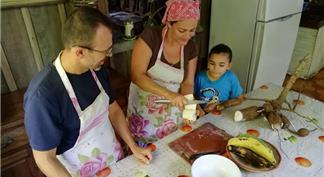 Woman peeling yucca in a traditional kitchen and a man and child