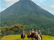 Panoramic view of group of five horseback riders and Arenal Volcano